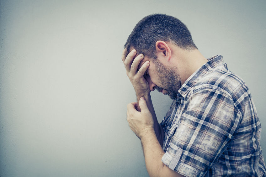 44059129 - portrait one sad man standing near a wall and covers his face at the day