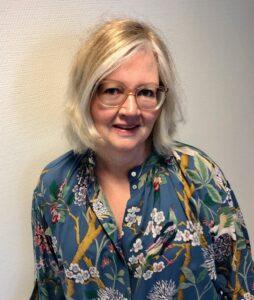 Bilde av lyshåret kvinne med briller, i blå bluse med blomster